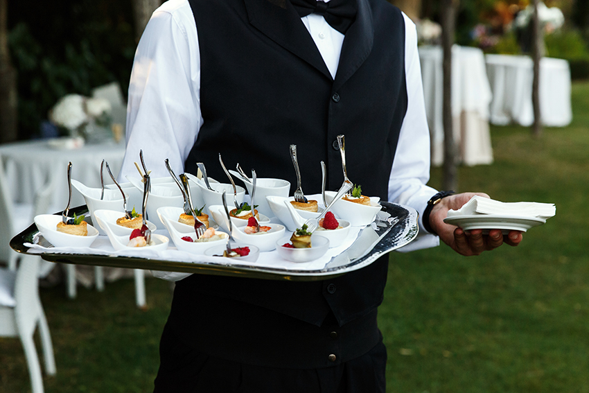 Waiter carries plate with tasty snacks